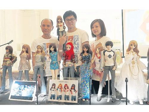 """周国栋(中)带着""""末永未来"""",偕同父亲周仰杰(左)及女设计师何佳潓,展示各种不同装扮的娃娃。"""