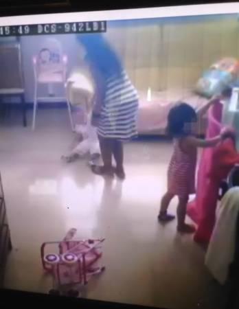 女傭單手拖著把男童的手臂,要他站起來。