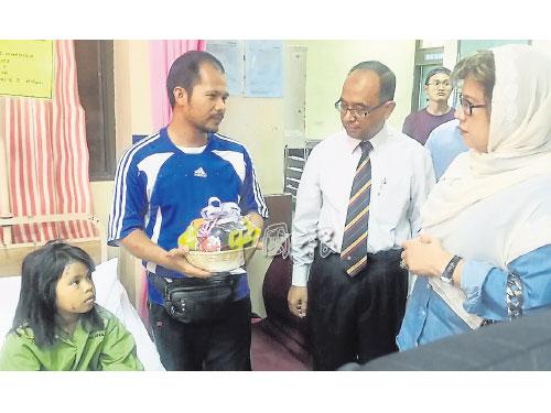 努魯愛諾(右起)與華希慰問受傷的女童愛妮,左2為女童父親海魯希山。