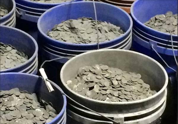 回收業者從垃圾中撿出大量硬幣。∕翻攝彭博新聞