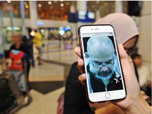 1名記者在吉隆坡國際機場,看著手機內的西瓦庫馬照片。(圖自馬來郵報在線)