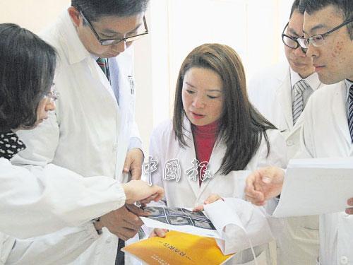 """香港媒體以""""醫學界的拼命三郎""""來形容鄺靄慧,圖為她在香港大學深圳醫院的病房內,與同僚認真討論病人進展的情景。"""
