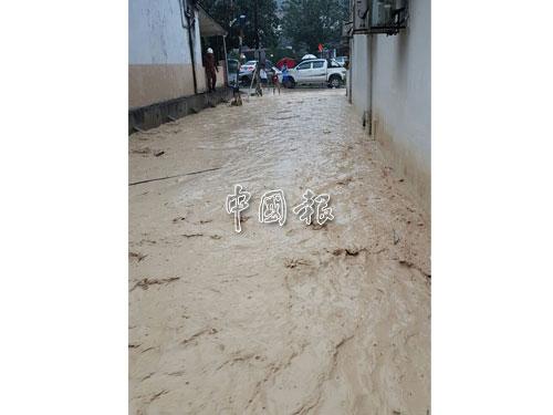 週日(19日)中午一場豪雨來襲,超過15戶居民傍晚忙著掃黃泥水。
