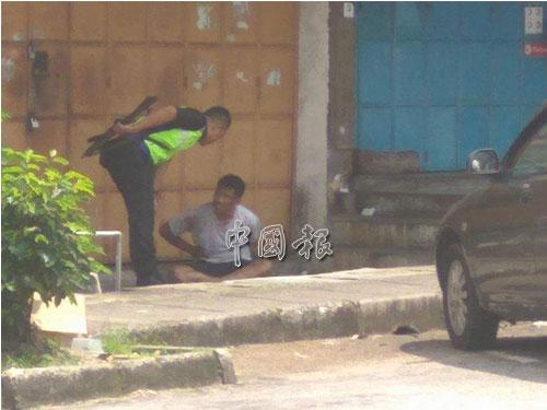 歹徒中彈後,束手就擒,并坐在地上等待救護車將他送往醫院治療。