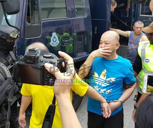黃長城被押下囚車時,左手被拷上手銬,他以右手遮掩鼻口,但全程沒有閃躲鏡頭。