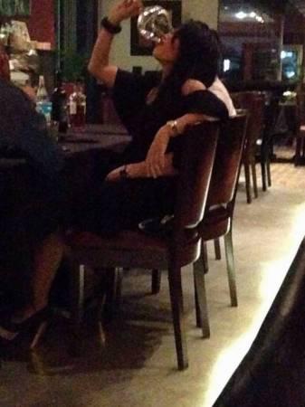 女子持紅酒杯暢飲,男子摟著女子的腰部。