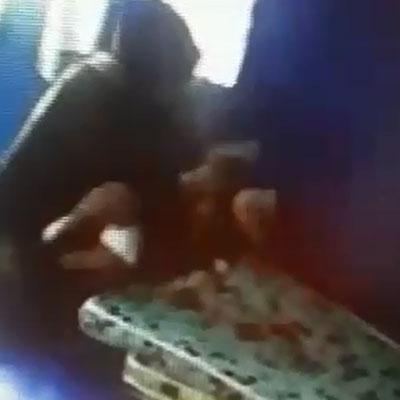 1名孩童躺在床上時,被1名保姆以雙手大力扯上來再丟回床上。(圖片截自視頻)