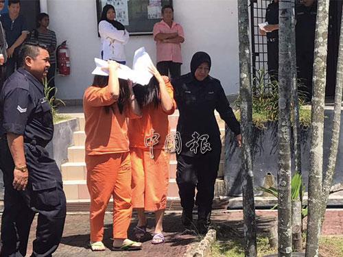 姐妹嫌犯離開法庭時,以紙張遮臉。