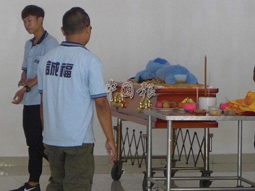 死者家人將一個布質玩偶放入棺木當陪葬品。