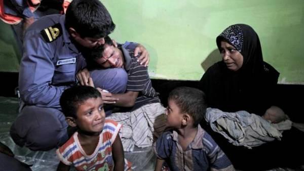 一名羅興亞難民抱著孟加拉警察大腿痛哭,央求不要遣返他全家人。