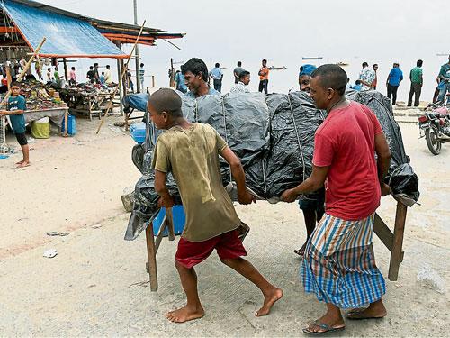強烈氣旋莫拉來勢洶洶,吉大港市的沙灘小販將檔攤移走。(歐新社)