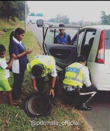 兩名熱心的交警路見不平,協助爆胎的印裔車主替換輪胎。
