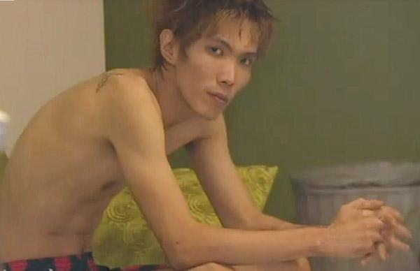 狮城男赤裸半身,肩上似乎有文身,淡定坐在床上。(取自9 News视频)