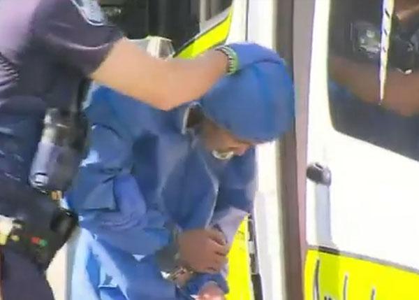 狮城男穿着一件浅蓝色的外套,双手上铐被押上警车。(取自9 News视频)