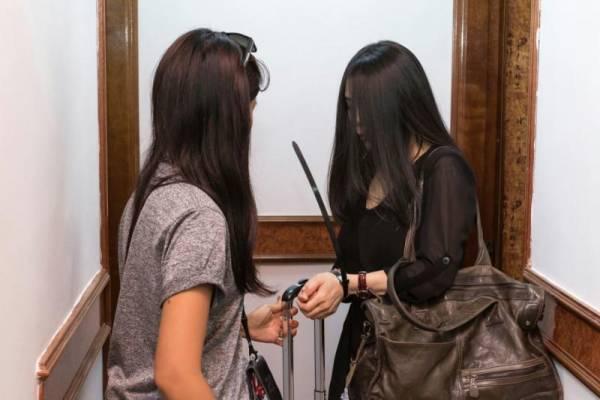 女警(左)用塑料扣帶扣住女郎雙方,把她押回警局調查。(警方提供)