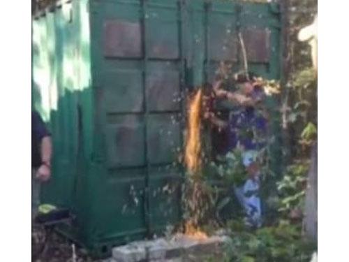 警方以電鋸和等工具嘗試打開貨櫃門。
