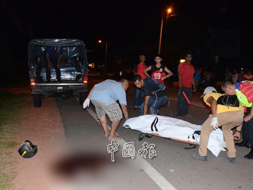 警方人員將死者遺體抬上警車,準備送往太平間。