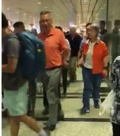 身穿橙色上衣的李顯龍和夫人何晶一同步出樟宜機場第三搭客大廈。