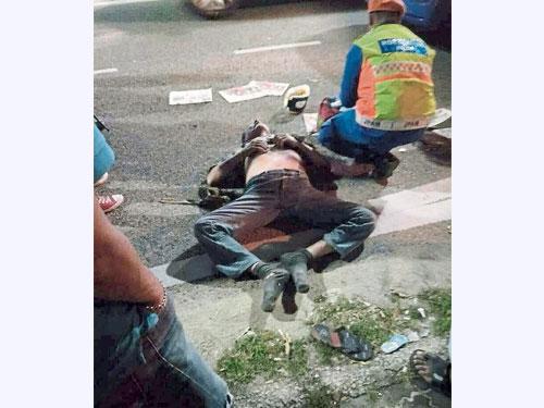 碰撞后,傷者躺在路上,醫務員赶到現場提供急救。(圖取自面子書)