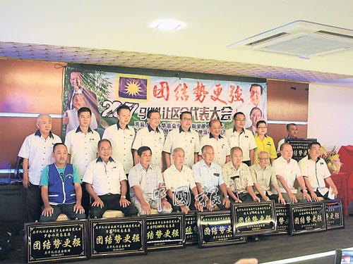 鄭修強(后排左4起)、廖中萊及吳池池等,頒發紀念牌匾給11位馬華元老。