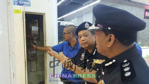 安華奧馬(右起)及再諾,指示國能職員拆下賭博中心的電箱。