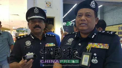 再諾(右起)及安華奧馬,手持電箱警告非法賭博業者,不要再繼續營業,否則警方將採取行動。