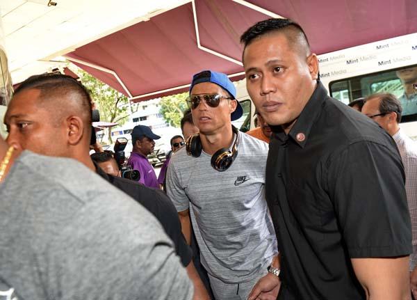 C羅納多(戴帽)抵達新加坡。(法新社)