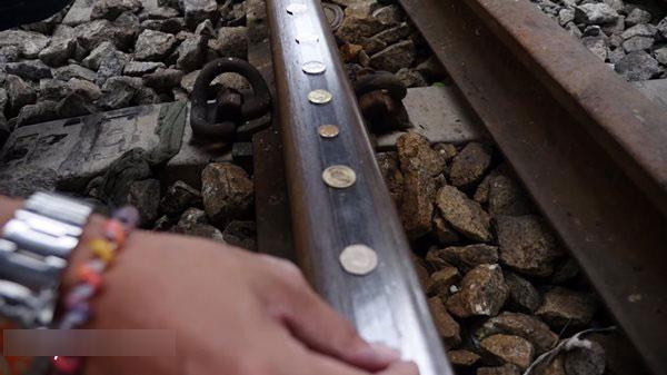 Nate把硬幣放在火車軌道上測試耐壓度