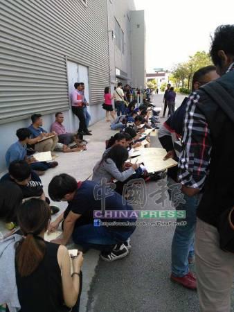 許多各族青年在場外席地而坐,填寫應徵表格。