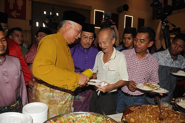 """納吉(左)化身""""服務員"""",親自為一名出席活動的華裔老伯,在食物上淋上辣椒醬。"""