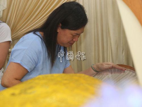 難忍喪夫之痛的莫桂美隔著棺罩,凝望著躺在棺木內的郭金福。