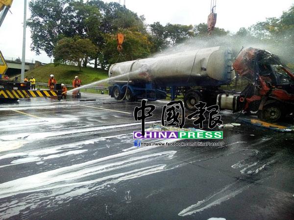 吊車把油槽羅厘吊起後,消拯員也往車身噴水,以防萬一。