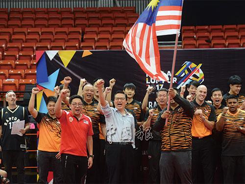 """男籃領隊魯本接過國旗後揮舞,鼓舞團隊士氣希望""""輝煌條紋""""能在頒獎禮上飄揚。"""