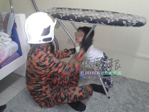 消拯員協助拉開燙衣板腳架鐵支,以讓女童脫困。