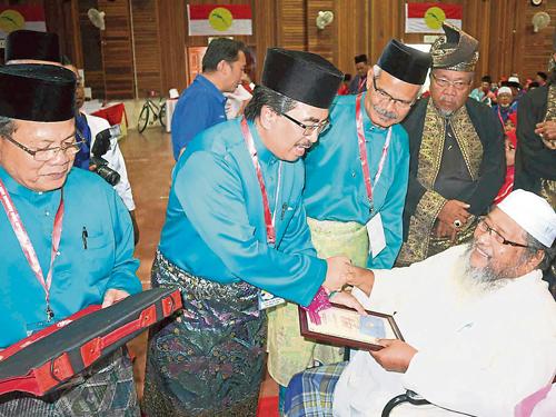 佐哈里(左2)在阿末韓查(左)陪同下,頒發感謝狀給巫統野新區部的其中一位元老。