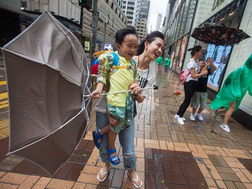 周三颱風來襲香港時,一對母子拿著雨傘避開風雨時,雨傘被吹到開花了。(歐新社)