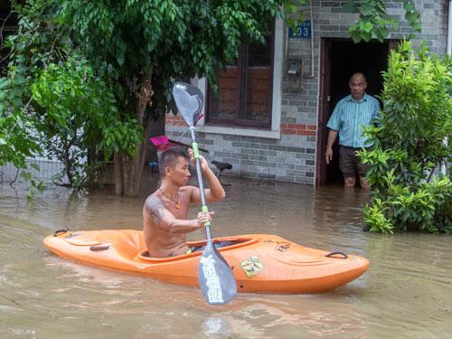廣東省廣州市周三有地方淹水,一名男子乘皮艇外出。(美聯社)