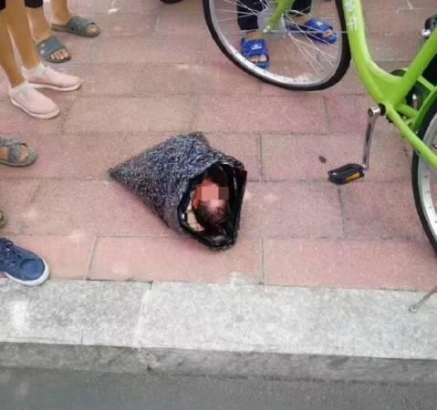 女嬰被放在黑色膠袋中。