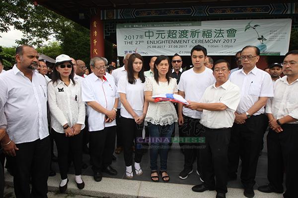 陳國偉(右3)移交黨旗給莫桂美(右5),感謝郭金福為行動黨的付出。左起為哥賓星、郭素沁、林吉祥、郭子雯、郭子毅、方貴倫及張健仁。