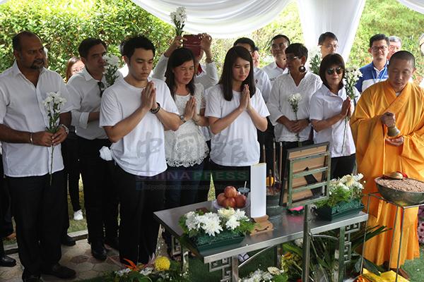 郭子毅(前排左起)、莫桂美及郭子雯雙手合十向他們敬愛的父親或丈夫道別,希望逝者安息。