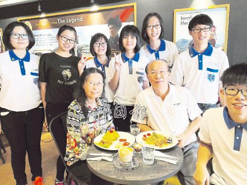 符貽錦(坐者右2)與妻子撥出時間,參與學生的校外義賣會活動,為學生加油打氣。