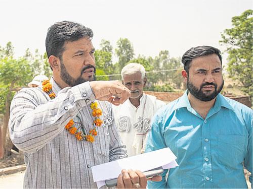 魯本(左)與他的隊友尼迪斯(Nitesh Singh)給我們解說在聖拉村莊進行的太陽發電系統計劃,后者是印度宣明會的策略聯盟與監管協調員,同時也在此行擔任咱們的翻譯員。