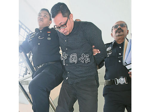 40歲被告峇德利希山(右)于星期一被帶往新山法庭,面對謀殺控狀前,全程彎下腰走路,避開媒體鏡頭。