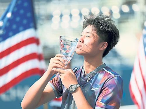 吴易昺称霸男双,也捧起男单冠军,成为青少年组双冠王。(新华社)