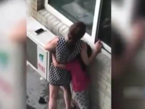 一對母女站在大樓外面的冷氣棚上。