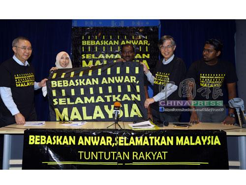 艾賽亞傑克(中)展示「釋放安華,拯救大馬」活動旗幟;左起為陳記光、努魯努哈、蔡添強及魯本。