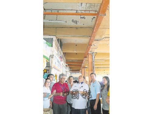 蕭開文(中)與市議員一起巡視巴剎,抬頭發現漏水的裂縫日益嚴重,右起為何彩思、林國堅,左起為葉小瑂和廖國賑。