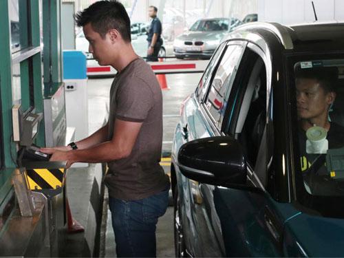 駕車人士下車到櫃檯呈交護照後,將雙手拇指放置在掃描儀器上。