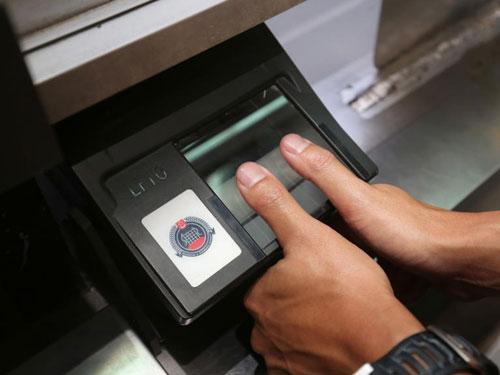 參與實驗的私家車,司機及6歲以上的乘客出入境時都必須下車掃描雙手拇指指紋通關。(聯合早報)