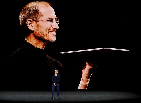 庫克站在大屏幕已故蘋果教主喬布斯前面,頗有傳承意味。(路透社)
